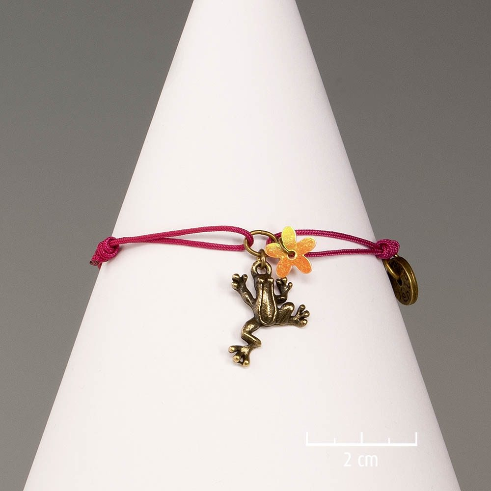 Bracelet ludique de nature poétique et cordon à nœud coulissant. Bijou lacet couleur fuchsia et grenouille bronze symbole de chance. Création Sébicotane, Zor Paris