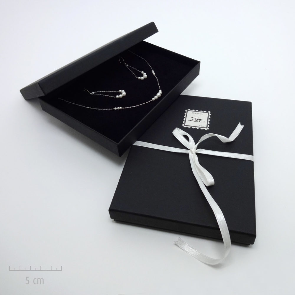 Emballage précieux, écrin noir pour un cadeau haut de gamme. Offrez un bijou dans un coffret noir et ruban blanc. Idée du luxe par Zor Paris 2