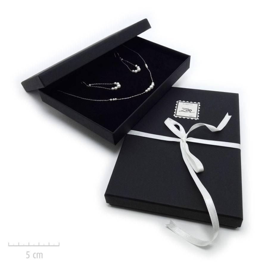 Un écrin noir habillé d'un ruban blanc. Emballage cadeau Vendôme de bijou Zor Paris. Broite, coffret, luxe.