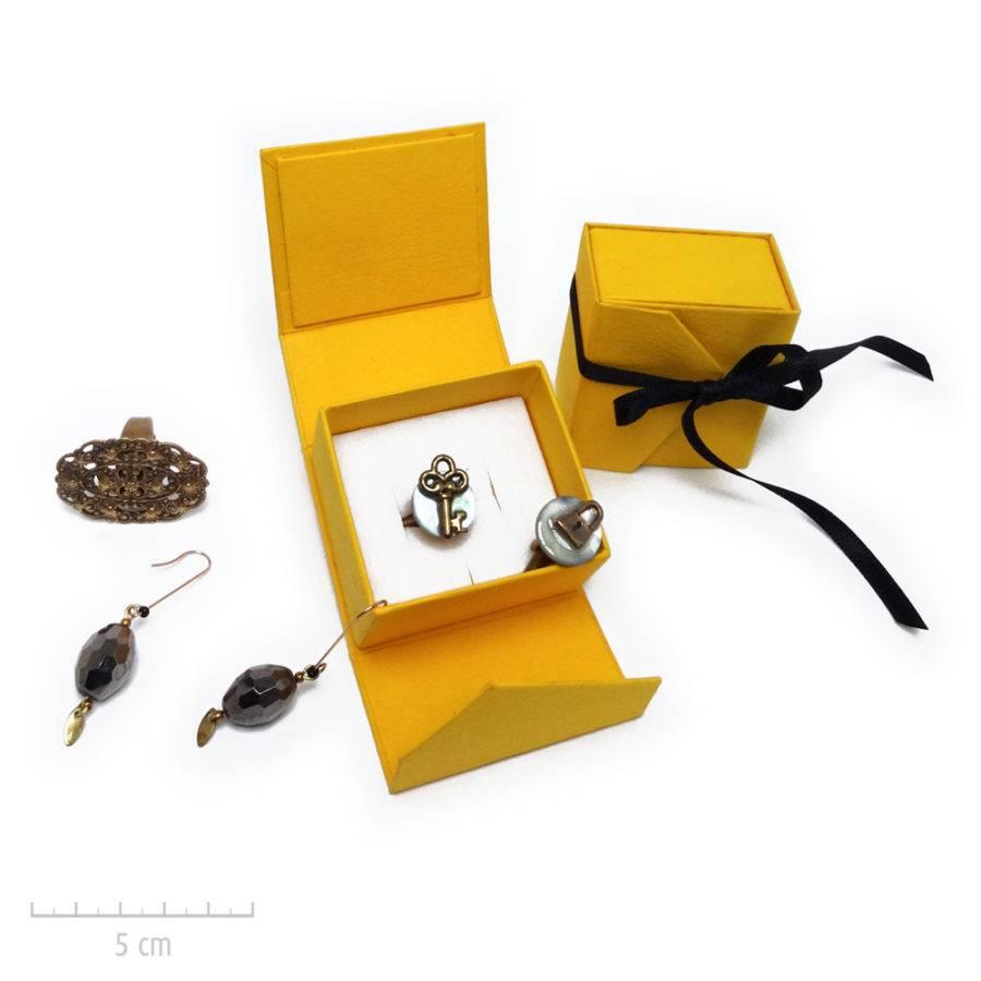 Un écrin jaune et blanc habillé d'un ruban noir. Emballage cadeau Vendôme de bijou Zor Paris. Broite, coffret, luxe.